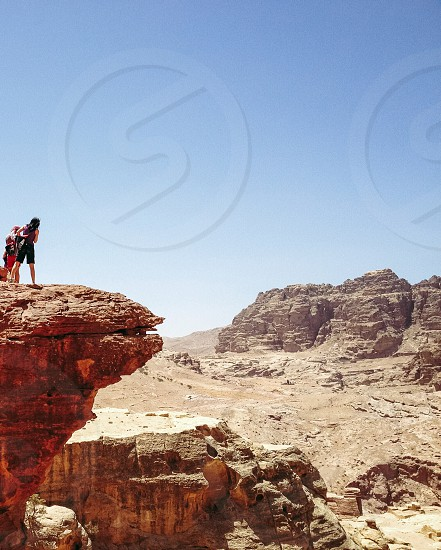 people standing on top of rock cliff in mesa photo