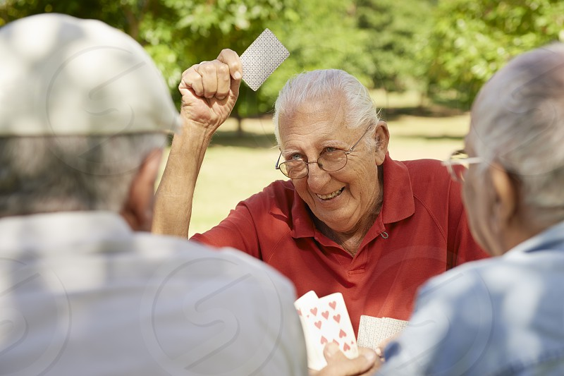 game; playing; cards; old; people; senior; laughing; 60s; 70s; active; aged; buddies; caucasian; cheerful; elderly; enjoy; free time; friends; fun; glad; grandfather; group; happiness; happy; hispanic; hospice; joy; latino; lifestyle; male; man; match; mates; men; natural; park; pensioner; persons; relaxing; retired; retirement; seniors; smile; smiling; three; together; white; winner; winning photo
