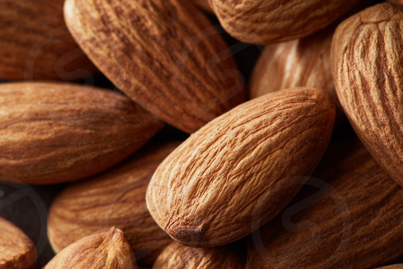 Macro view of many almonds lying one upon the other and forming a background photo