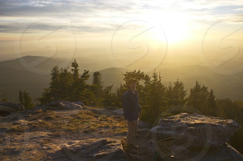 person in blue sweater standing on cliff facing sunrise photo