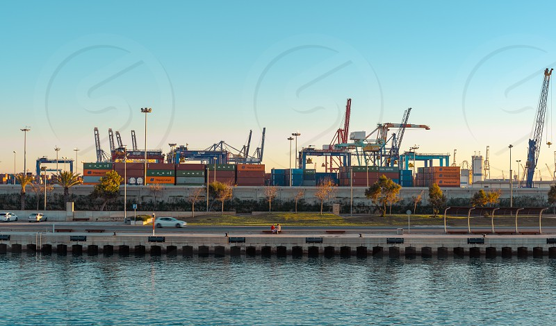 Valencia Spain – December 08  2018:  View of Valencia port across the channel Valencia Spain. Cranes and containers.  Sunset. photo