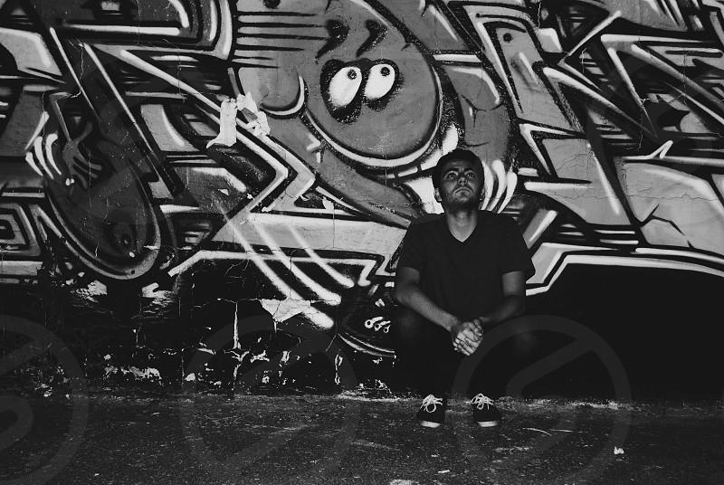 man in black shirt sitting near graffiti wall photo