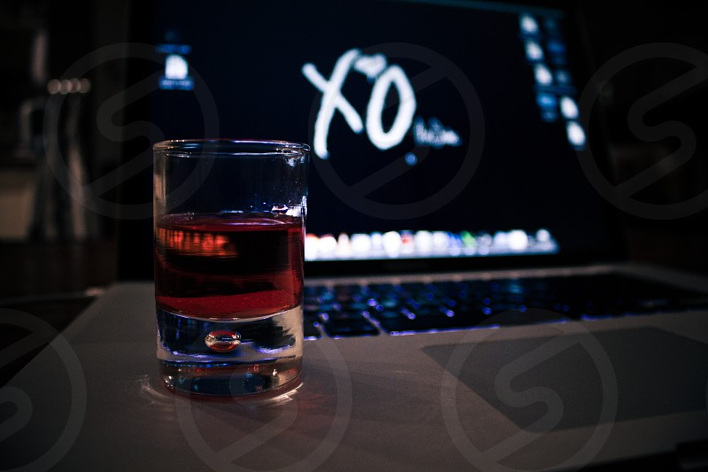 a alcoholic drink with candy in it. In the background a macbook. photo