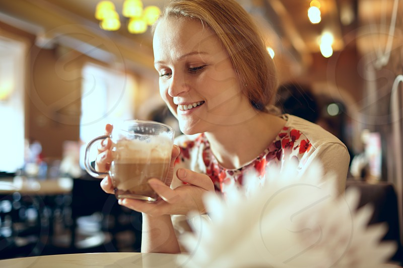 Portrait of girl enjoying coffee latte in cafe. Beautiful vintage interior in blur with natural sunlight. photo