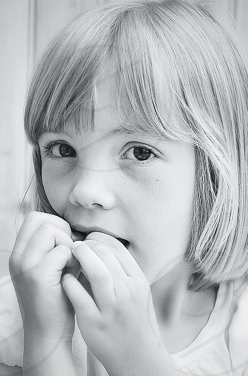 girl in white shirt biting nails photo