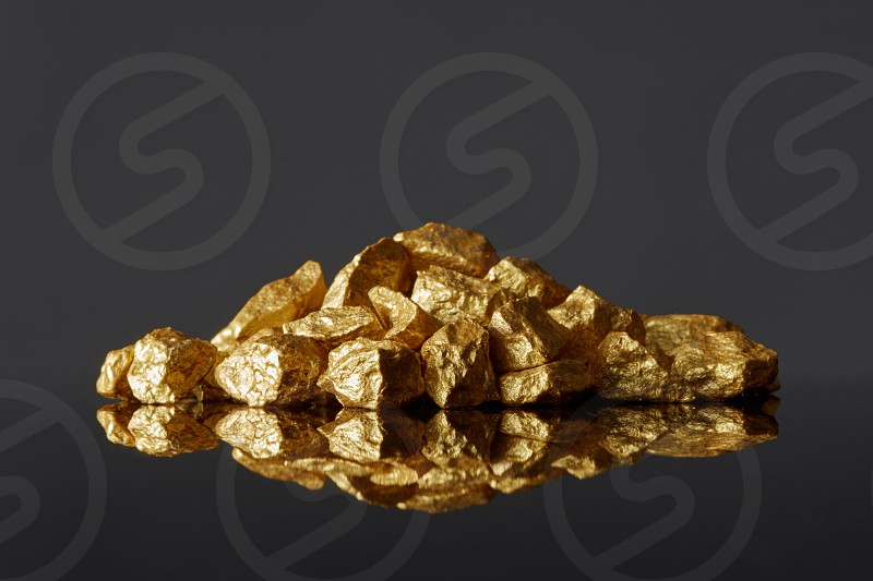 Close up of mound of gold nuggets on a black reflective surface background. Concept of financing and Noble metal photo