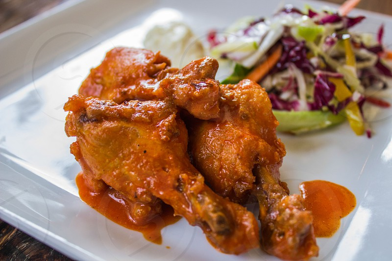 Chicken wings on white plate with marinated vegetables in background. Red sauce. photo