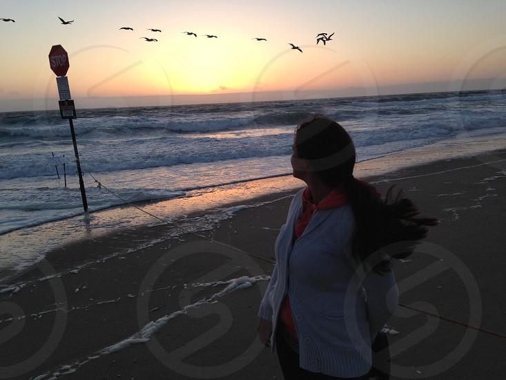 woman wearing white sleeved cardigan staring at flying flock of birds on beach shoreline photo