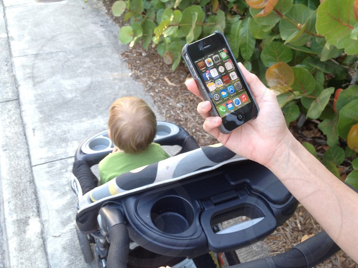 person holding a black iphone while pushing a baby stoller photo