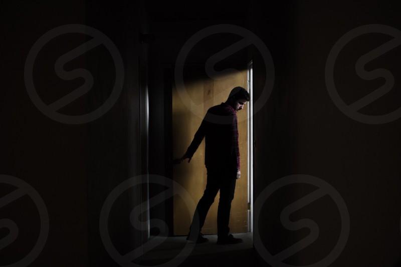 man standing beside brown wooden door photo