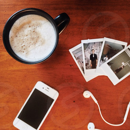 A cup of coffee an iPhone 4S four Instax Mini photos and some EarPods. photo
