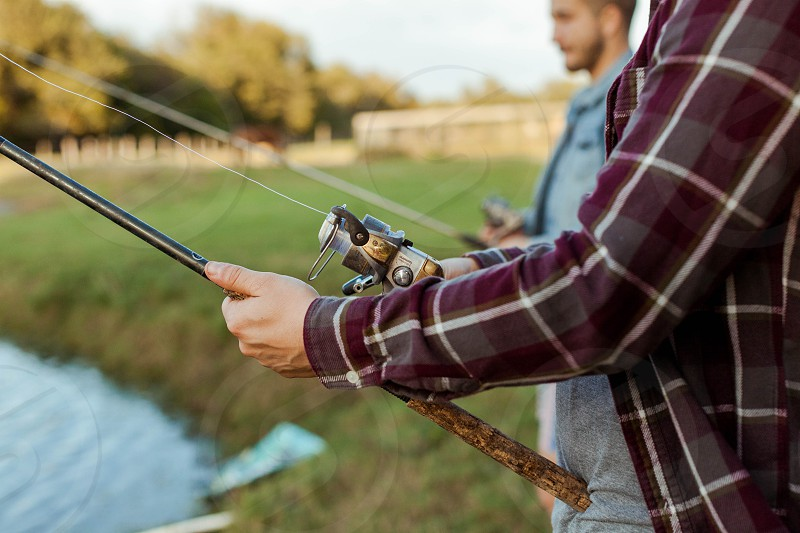 Man in flannel shirt holds a fishing rod in front of small pond photo