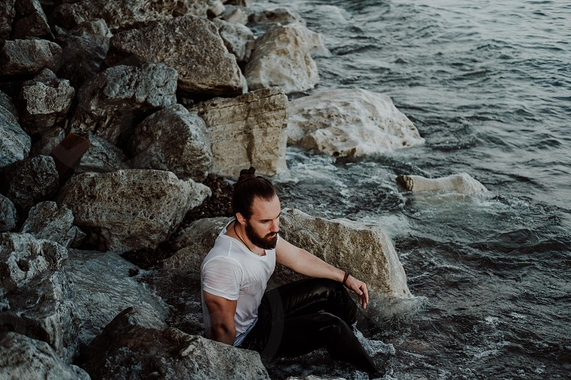 Man with bun in white t shirt and black denim jeans sitting in rocks and water photo
