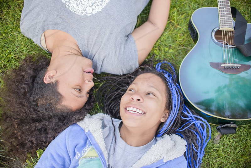 2 persons lying on grass lawn with acoustic guitar in their side photo