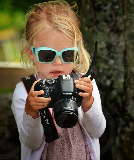 little girl holding a canon dslr camera photo