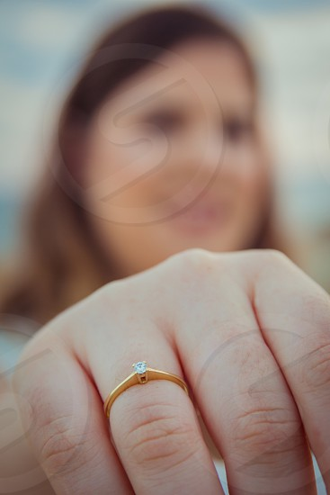 Happy woman shows off her new engagement ring on her finger. Closeup blur background. photo