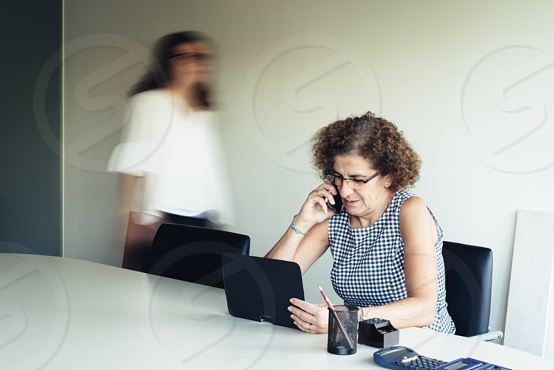 Businesswoman using mobile phone and tablet sitting at desk in office. photo