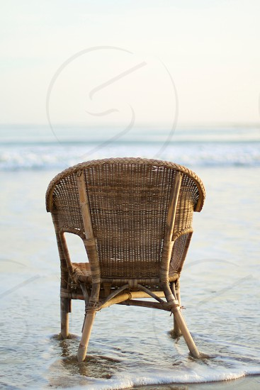 brown woven chair at the seashore photo