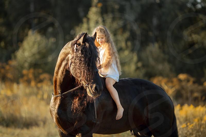 Little ballerina girl with black fresian stallion  photo