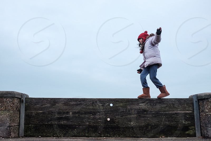 Girl balancing on a wooden sea barrier wall in winter coat and hat photo