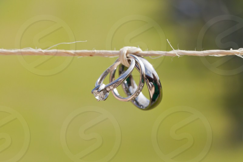 Wedding rings tied on a string with green field in the background.  photo