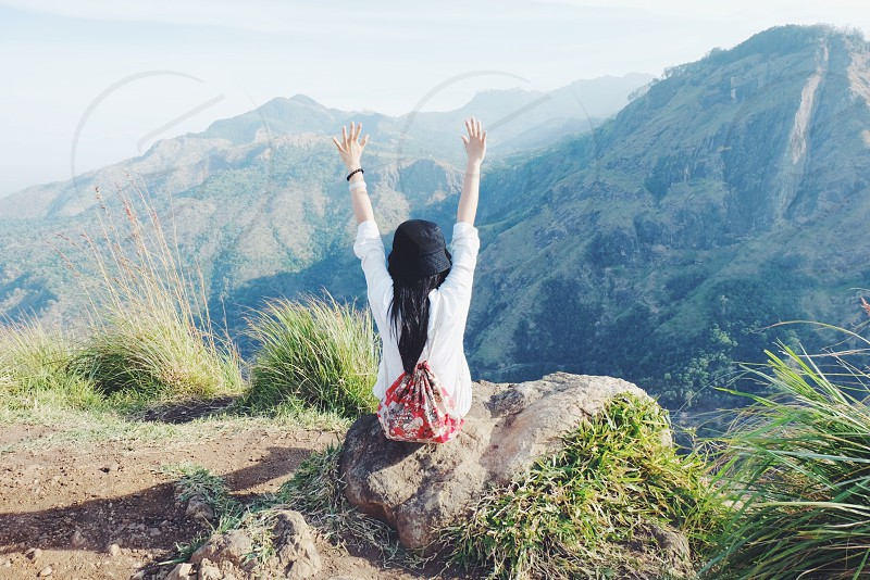 black haired woman in white long sleeve shirt with red and white floral drawstring backpack and black hat sitting on rocky mountain ledge with arms in air photo