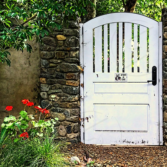 Rustic white gateWhite gate on a Stone wall and a rural location photo