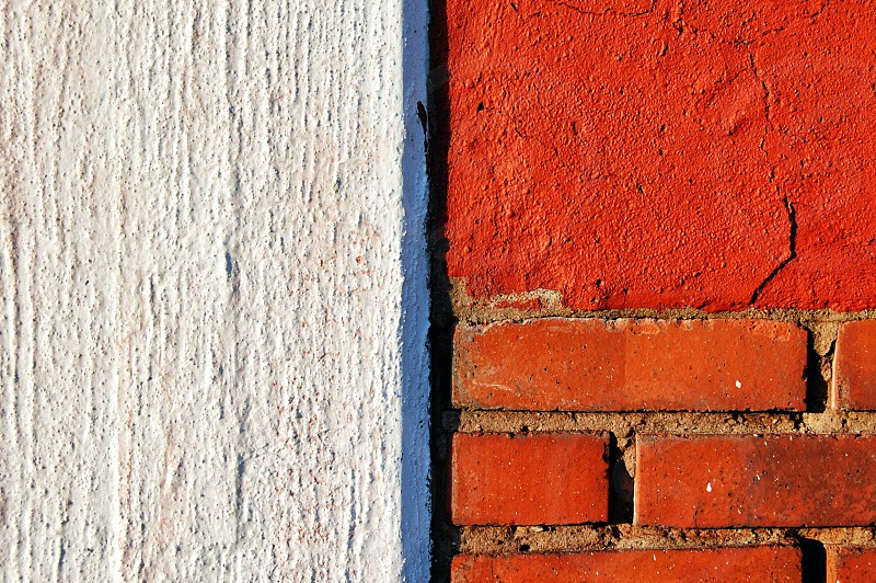 view of red brick wall beside white concrete wall photo