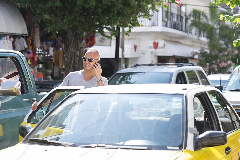 Male tourist in Puerto Vallarta Mexico is talking on his phone while entering a taxi cab. Man 55 years old hispanic ethnicity. Busy traffic. photo