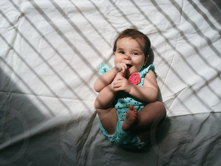 baby in green and black printed blouse photo