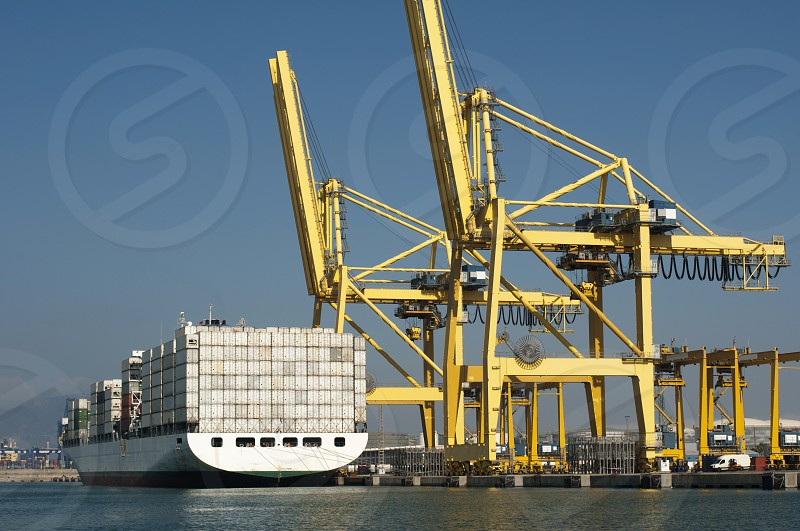Freighter in port being loaded with containers.Cranes in port photo