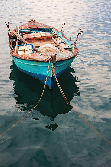 One old fishing boat with nets and other equipment in sea water. photo
