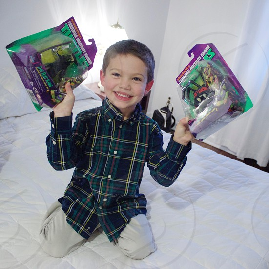 boy in black and brown button up dress shirt holdinng teenage mutant ninja turtle action figure photo