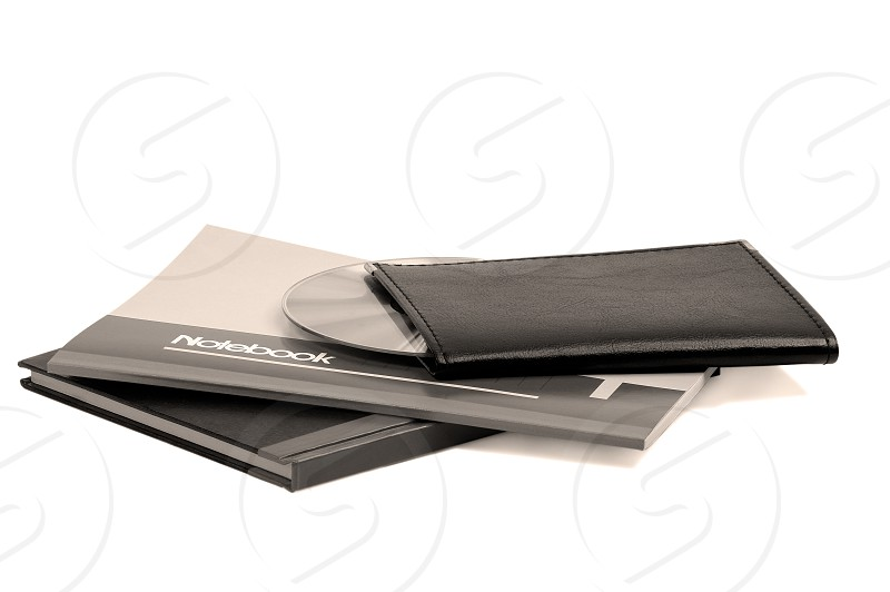 assorted notebooks with a cd flat piled on white backgroundsepia filter photo