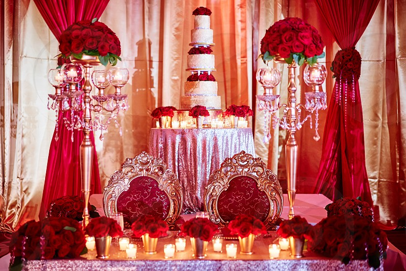 The seat for bride and groom of luxury indian wedding with wedding cake in background decoration with red roses theme and candle light in the sangeet night party photo