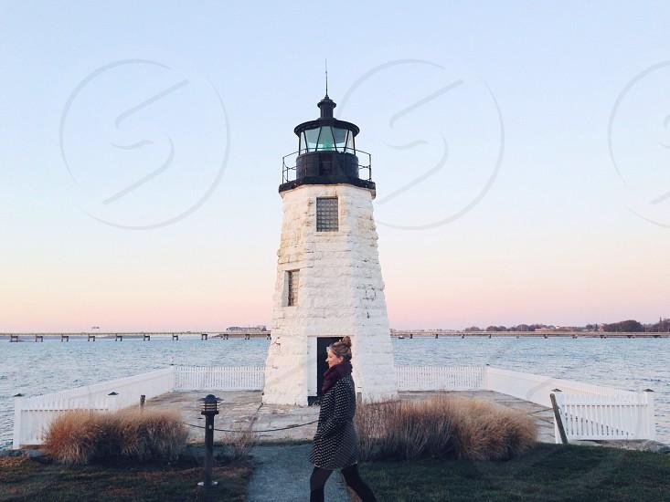 woman in gray jacket walking near light tower photo