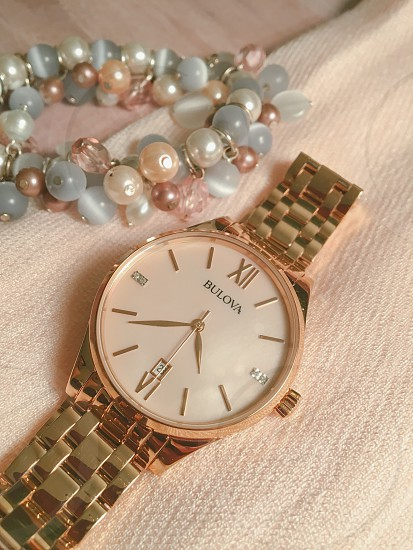gold link bracelet round bulova analog watch at 4:39 photo