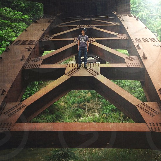 man standing at metal bridge photo