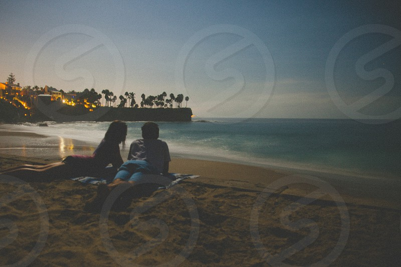 man and woman lying on a blue mantle on sand on shore photo