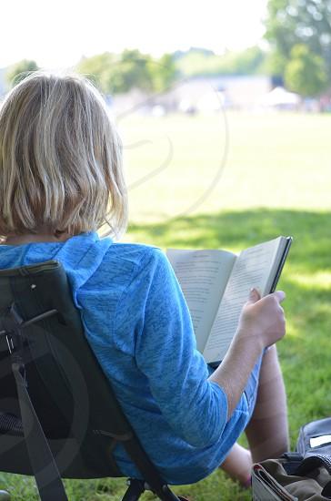 Girl reading book outside photo