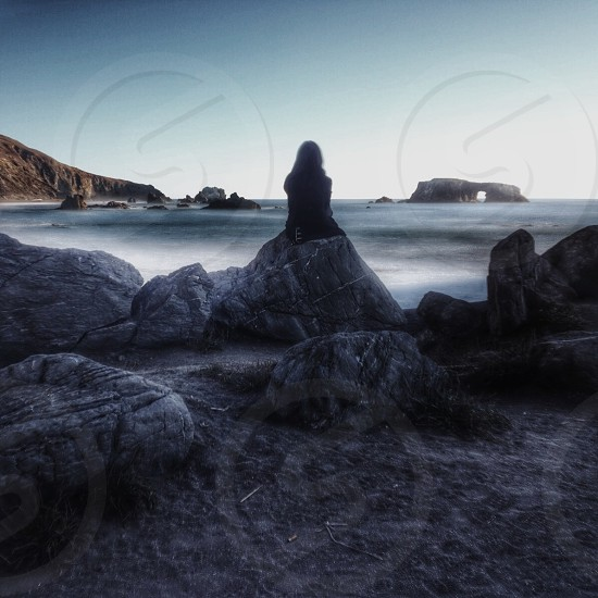 woman sitting on grey rock silhouette photo