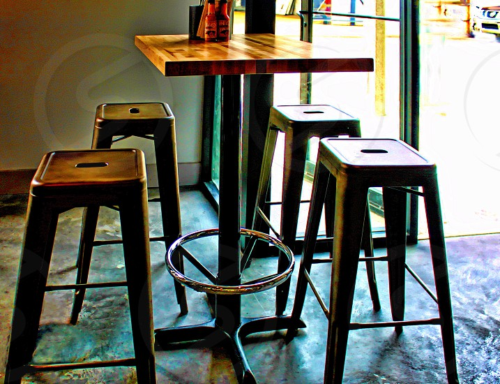 Set of metal stools around a small table at a cafe. photo