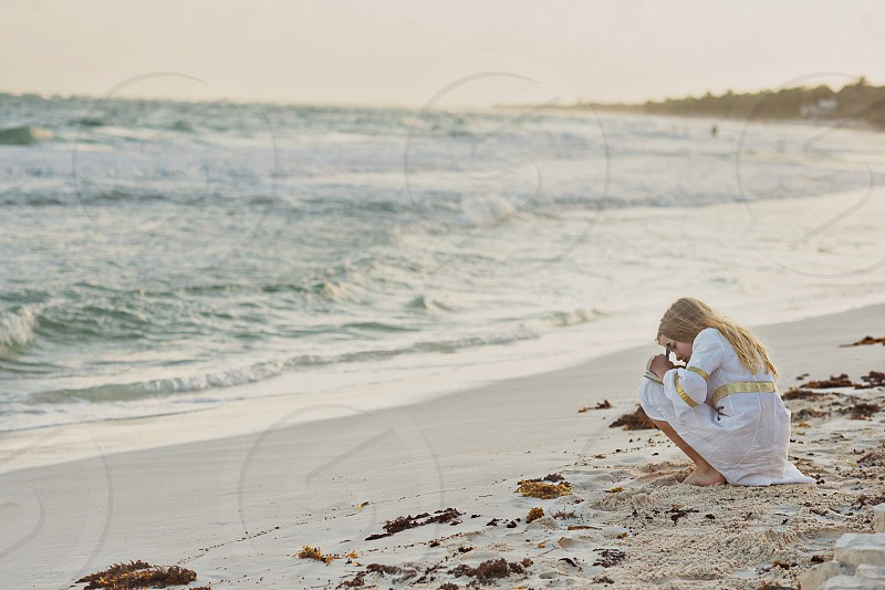 Girl writing letter at the ocean photo