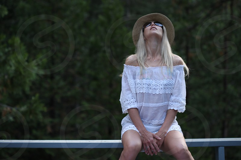 woman wearing white off shoulder blouse sitting by the white railing photo