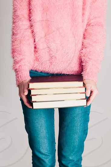 Young girl holding a few books. Teenager girl wearing pink sweater and blue jeans. Vertical photo photo