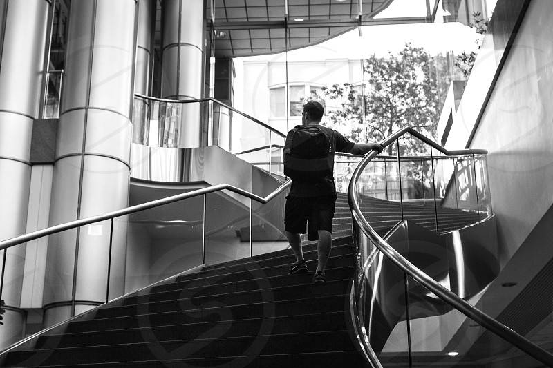 grayscale photography of a man in black shirt walking up stairs during daytime photo