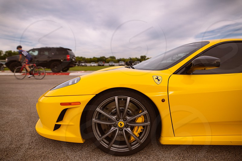 yellow ferrari at a race track with bicycle in background and cloudy sky photo