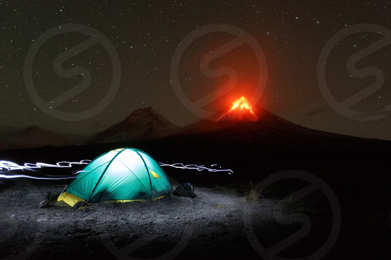 Night mountain landscape of Kamchatka Peninsula: illuminated tourist camping on background eruption volcano light from headlights around tent. Russian Far East Kamchatka Region Klyuchevskoy Volcano photo