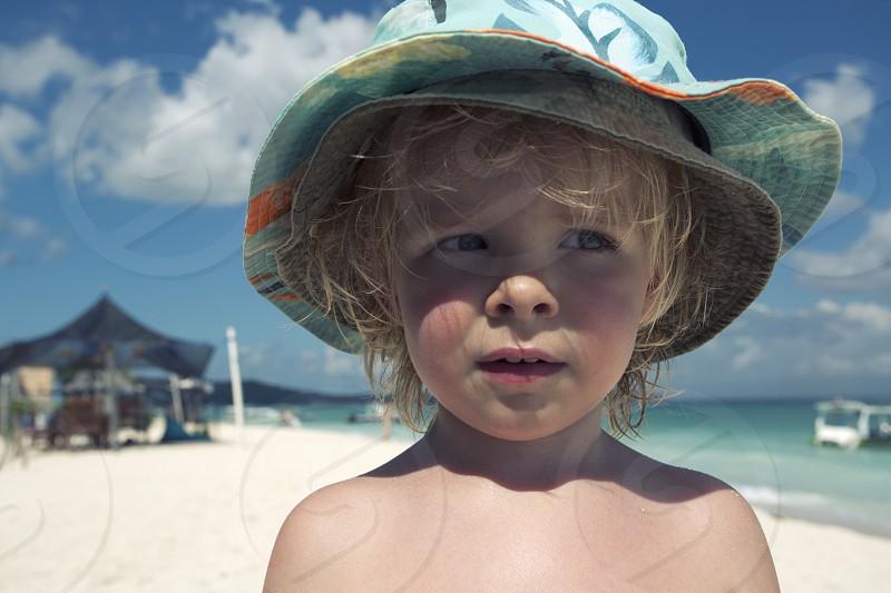 Toddler boy blonde Indonesia Bali nusa lembongan beach holiday travel sun summer hot. photo