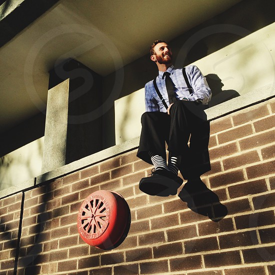 man in suspenders and dress pants sitting on brick wall photo